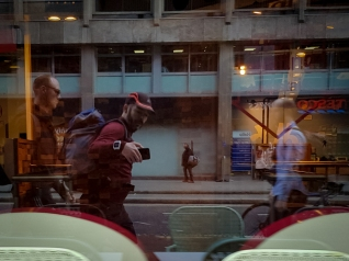 A run commuter with a backpack reflected in a shop window